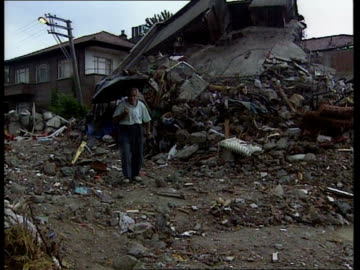 search and rescue scaled down; more survivors found: search and rescue scaled down; itn raining gv man towards down wreckage of house holding... - 性感染症点の映像素材/bロール