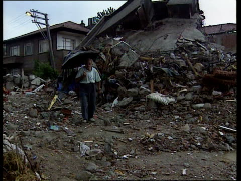 search and rescue scaled down more survivors found search and rescue scaled down itn raining gv man towards down wreckage of house holding umbrella... - geschlechtskrankheit stock-videos und b-roll-filmmaterial