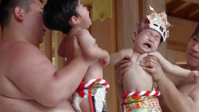 stockvideo's en b-roll-footage met more than 100 babies face off in a traditional crying sumo ring in an annual event believed to bring infants good health in japan - worstelen