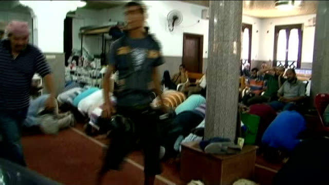 More than 600 people killed in military crackdown Aftermath EGYPT Cairo INT Woman screaming in grief comforted by other woman inside Iman mosque Men...