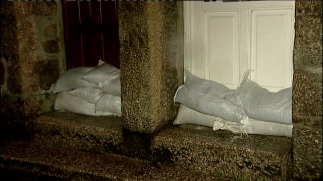 more wet weather forecast to add to christmas flooding woes; england: cornwall: helston: ext at night rain falling in village sandbags stacked by... - inch stock videos & royalty-free footage
