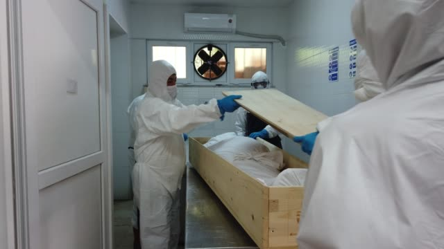 vídeos y material grabado en eventos de stock de morgue workers wearing personal protective equipment tend to a deceased person at the zincirlikuyu morgue on may 15, 2020 in istanbul, turkey. with... - muerte