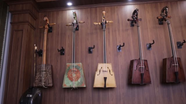 morin khuur are displayed in a khanmusic llc shop in ulaanbaatar mongolia on august 11 2017 photographer taylor weidman shots wide shot of six... - music stand stock videos & royalty-free footage
