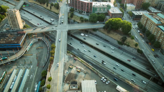 A morning aerial time lapse of traffic on several roads in Seattle, Washington, including Interstate 5 and four surface street overpasses, featuring glimpses of the Capitol Hill neighborhood and the Convention Center bus depot.