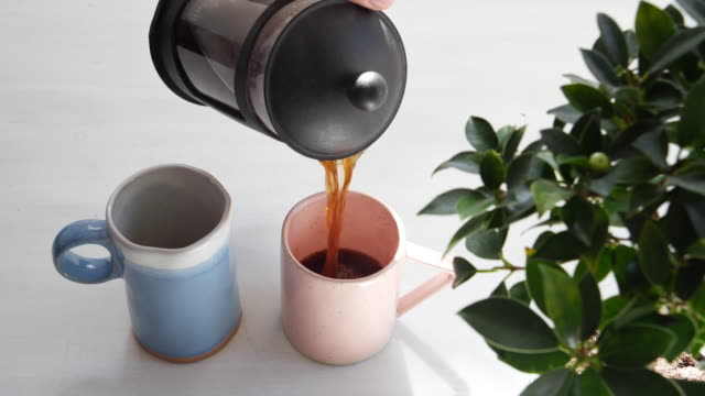 morning coffee being poured from a french press into blue and pink mugs for a couple - coffee table stock videos & royalty-free footage