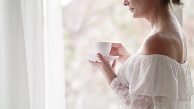 vidéos et rushes de café du matin par la fenêtre - robe blanche