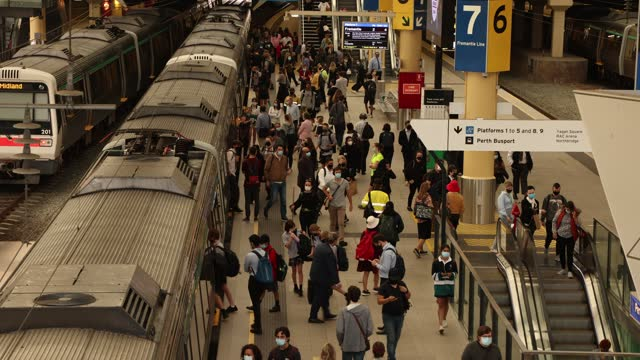 morning commuters are seen on a platform at the perth train station wearing face masks on april 27, 2021 in perth, australia. lockdown restrictions... - フリーマントル点の映像素材/bロール