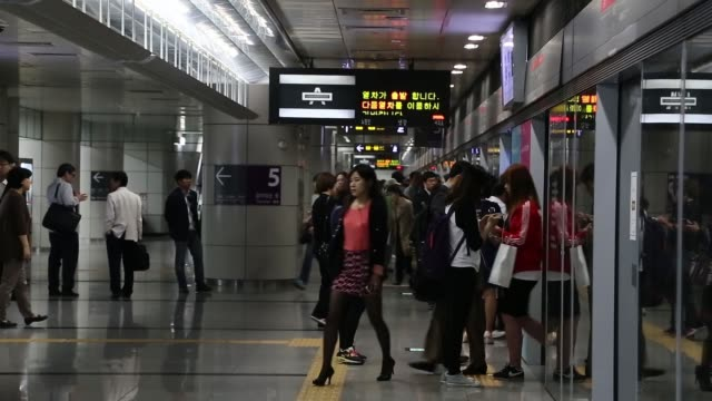 stockvideo's en b-roll-footage met morning commuters exit a subway station in the yeouido financial district in seoul morning commuters wait at a subway station platform as a crowd of... - metro platform
