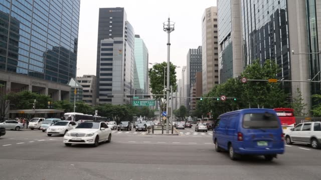 morning commuters walk across a pedestrian crossing on teheranno street in the gangnam district of seoul, wide shot traffic moves along teheranno... - moving up点の映像素材/bロール