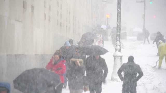 morning commuters walk on snowy street during the snowstorm at lower manhattan on feb. 09 2017. - blizzard stock videos & royalty-free footage