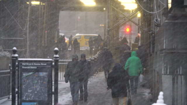 morning commuters walk on wall street around the new york stock exchange during the snowstorm on feb. 09 2017 at nyc. - umbrella stock videos and b-roll footage