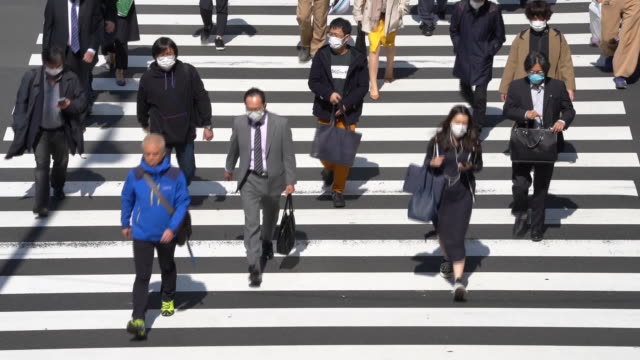 morning commuters wearing protective masks walk in front of shimbashi station in tokyo japan on wednesday april 8 2020 - japan bloomberg stock videos & royalty-free footage