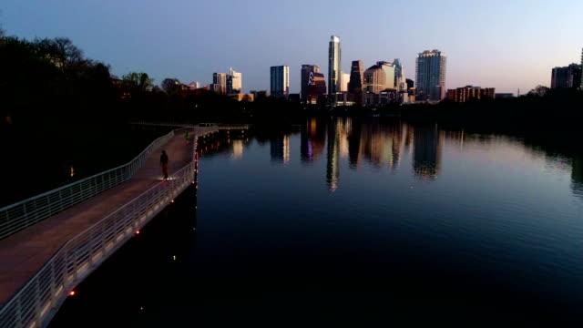 vídeos de stock e filmes b-roll de morning exercise on riverside pedestrian bridge with sunrise mirrored image austin texas capital city - town