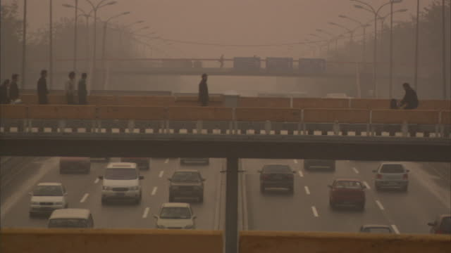 SLO MO MS Morning highway traffic in smog, pedestrians and cyclists passing above on overpass, Beijing, China