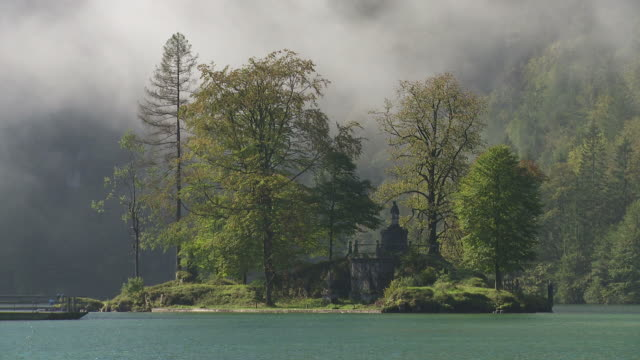 morning mist clearing over little island in lake - zeitraffer stock videos & royalty-free footage