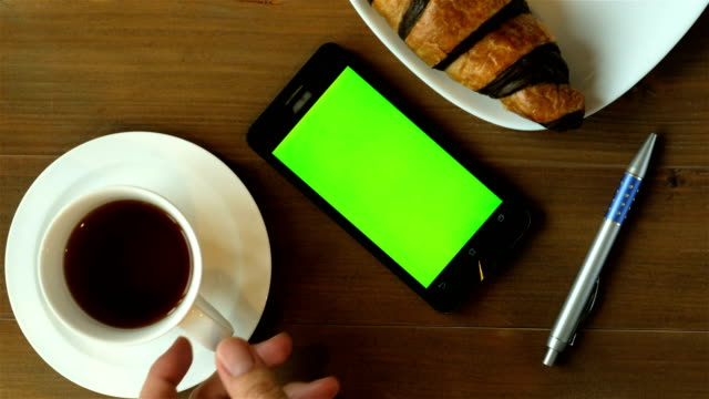 morning news with coffee - coffee cup and chocolate croissant on wood table with green screen smart phone. - table stock videos & royalty-free footage
