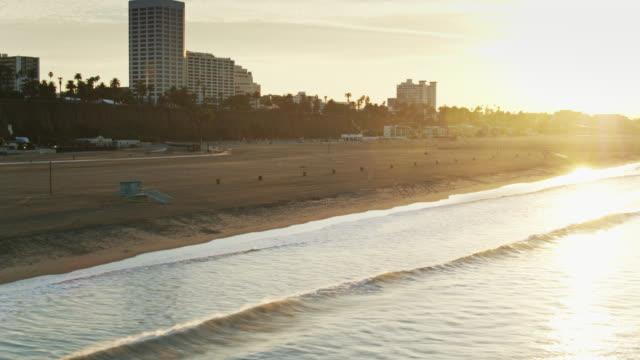 vídeos de stock, filmes e b-roll de raios da manhã brilhando na praia de santa monica - drone shot - santa mônica