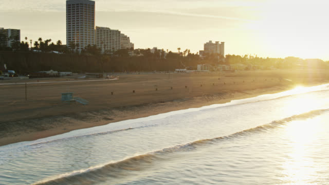 vidéos et rushes de morning rays shining down sur santa monica beach - drone shot - santa monica