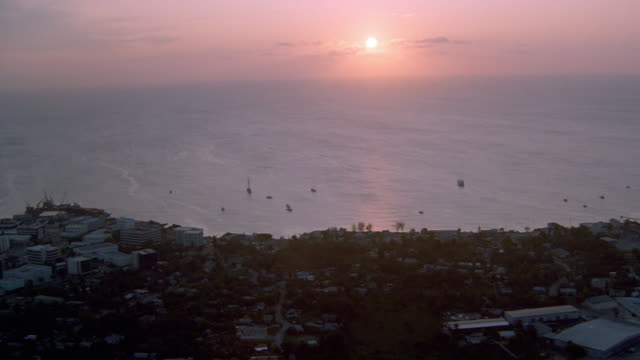 vidéos et rushes de a morning sun casts pink light across the caribbean sea off the coast of the cayman islands. - angle de prise de vue