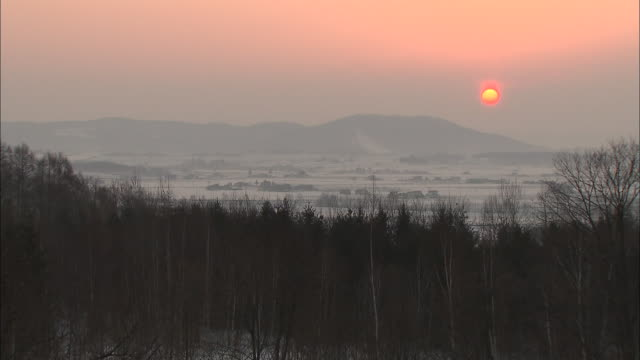 a morning sun glows through a hazy sky over a mountain and snow-covered farmlands. - 30 seconds or greater stock videos & royalty-free footage
