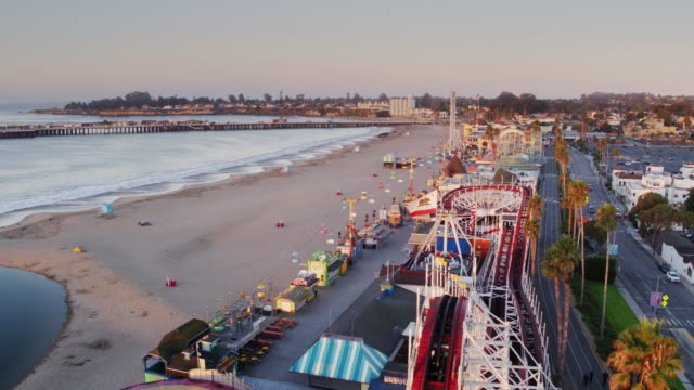 morning sunlight shining on santa cuz boardwalk - drone shot - santa cruz california stock videos and b-roll footage
