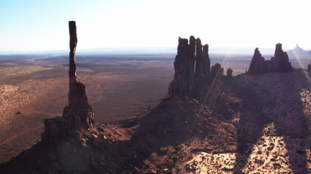 vidéos et rushes de matin du soleil brillant à travers totem pole et yei bi chei, monument valley - prise de vue aérienne - utah