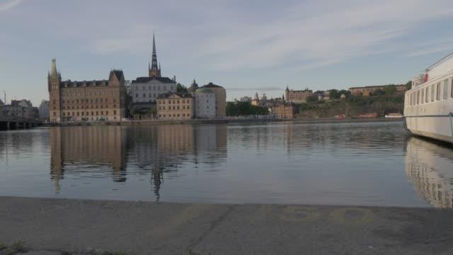 vídeos de stock e filmes b-roll de morning view of gamla stan from harbour near town hall, stockholm, sweden, scandinavia, europe - edifício do governo local