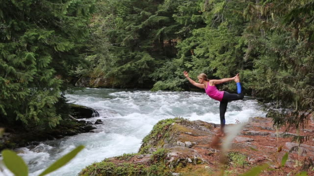 morning yoga on the rocks above the river - posture stock videos & royalty-free footage