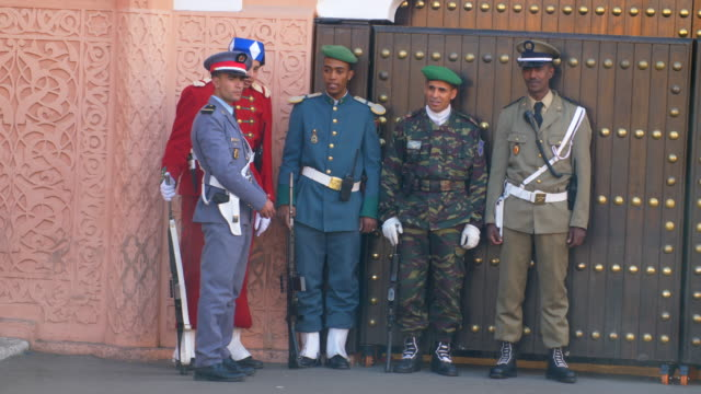 vidéos et rushes de moroccan army soldiers in colourful uniforms standing sentry in the street in marrakech - maroc