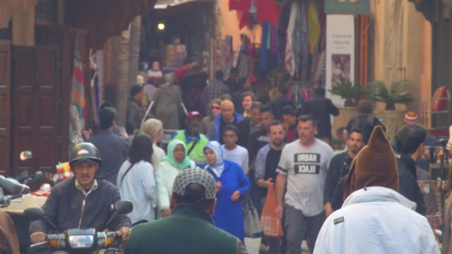 vídeos de stock e filmes b-roll de moroccan souk - large crowds walk through the narrow streets past market stalls and arab craft traders - marrocos