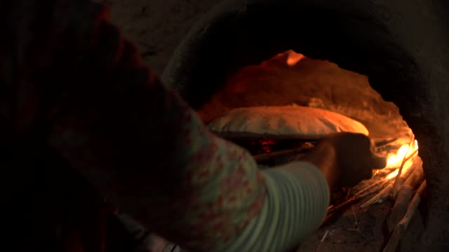 moroccan woman tending fire then bread in stone oven - stein stock-videos und b-roll-filmmaterial