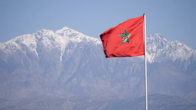 vídeos de stock e filmes b-roll de morocco flag blowing in the wind with atlas mountains and snowy peaks in background - marrocos