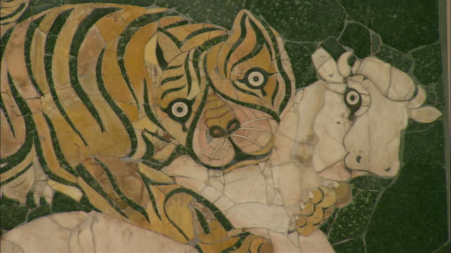 a mosaic at the colosseum in rome depicts a tiger attacking a bull. - mosaic stock videos and b-roll footage