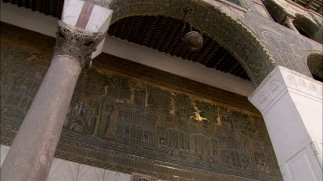 A mosaic frieze decorates the wall in a covered walkway at the Umayyad Mosque Damascus. Available in HD.
