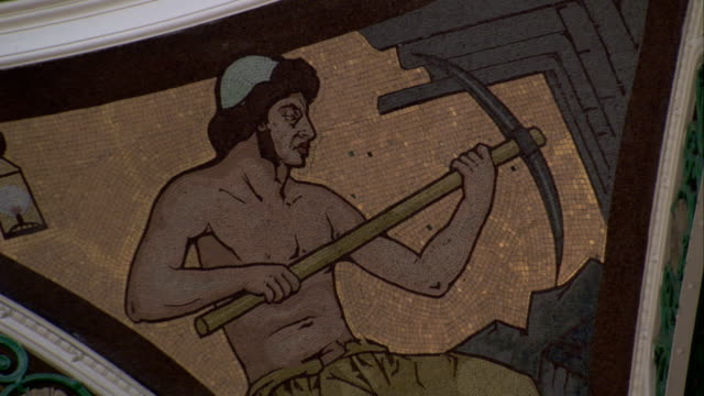 A mosaic in the ceiling of a Victorian building depicts a man with a pickaxe. Available in HD.