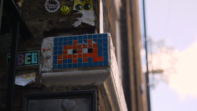 a mosaic tile artwork by street artist invader is surrounded by stickers and other artworks, brick lane - east london stock videos and b-roll footage