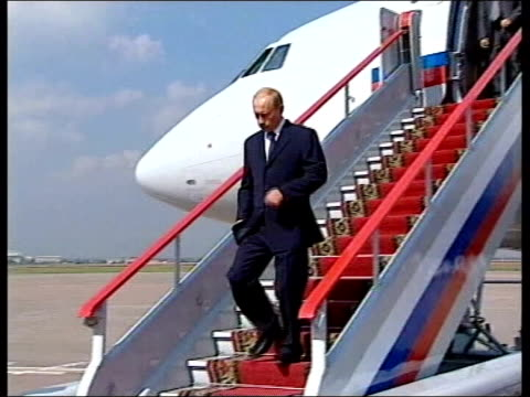 Russian President Vladimir Putin down steps from plane as greeted by officials Putin along with others