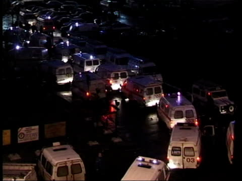 crime/ conflict moscow siege theatre stormed ext at night police on street as ambulances past tgv ambulances lined up outside with flashing lights... - belagerung stock-videos und b-roll-filmmaterial