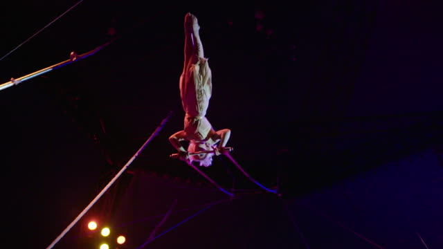 acrobatic trapeze act slow motion - akrobat stock-videos und b-roll-filmmaterial