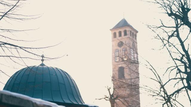 stockvideo's en b-roll-footage met moskee en de toren van de klok naast elkaar in het centrum van sarajevo, tijdens een zonnige de zomerdag - klokkentoren met wijzerplaat