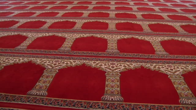 mosque architecture panleft on a massive prayer rug in a mosque hall with a scrolled gold arch design on a red background - flooring stock videos & royalty-free footage