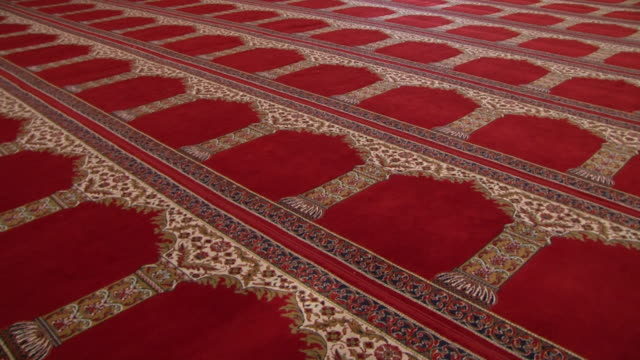 mosque architecture panright on a massive prayer rug in a mosque hall with a scrolled gold arch design on a red background - flooring stock videos & royalty-free footage