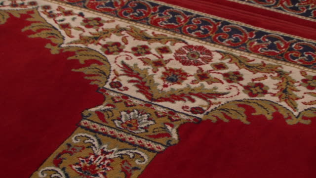 mosque architecture cu tiltdown on the ornate design of a prayer carpet in a mosque hall showing a gold column and arches on a red background - decoration stock videos & royalty-free footage