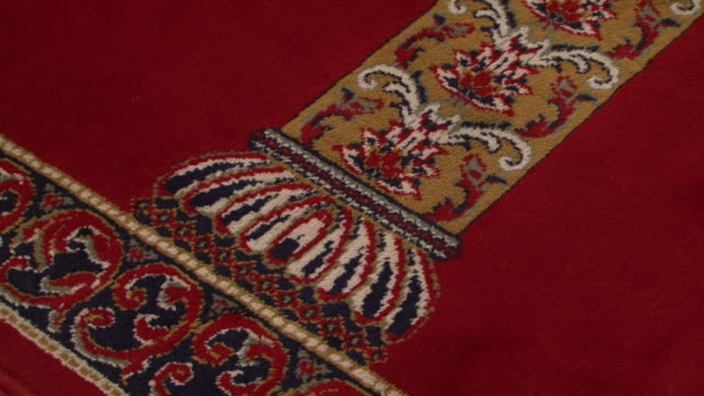 mosque architecture cu tiltup on the ornate design of a prayer carpet in a mosque hall showing a gold column and arches on a red background - flooring stock videos & royalty-free footage