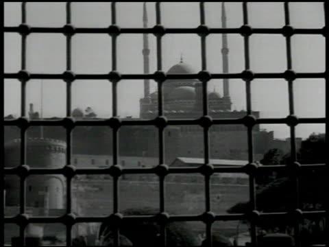 mosque beyond gated window covering. lahore, pakistan: xws badshahi masjid w/ huge courtyard filled w/ praying muslims . muslims rising from prayer.... - lahore pakistan stock videos & royalty-free footage
