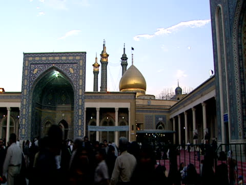 la mosque iwan, minarets and golden dome with crowd of visitors in the courtyard / qom, iran - shi'ite islam stock videos & royalty-free footage