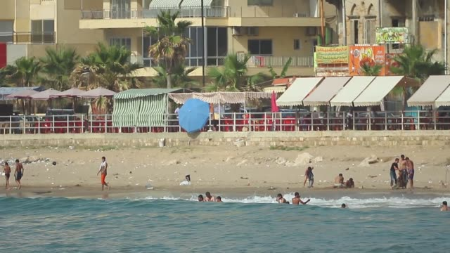 mosque with green minaret, jet ski, man with tattoo, boys and men swimming, men on small fishing boat, apartment buildings behind mosque, ancient... - minaret stock videos & royalty-free footage