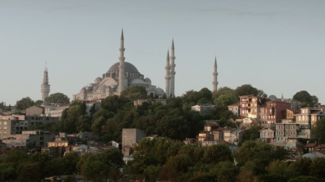 ws mosques in cityscape at dawn or dusk, with minarets and dome against soft sky - {{ contactusnotification.cta }} stock-videos und b-roll-filmmaterial