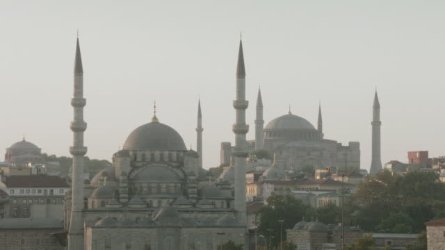 ws mosques in cityscape during dawn or dusk, with minarets and domes against soft sky - {{ contactusnotification.cta }} stock-videos und b-roll-filmmaterial