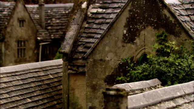 moss clings to weathered rooftops of stone cottages, bourton-on-the-water. available in hd. - weathered stock videos and b-roll footage